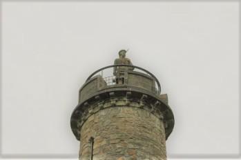 13 Highlander wearing kilt on top of monument